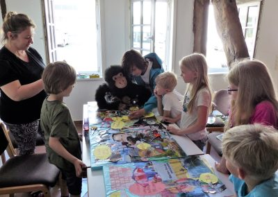 Die Kinder erarbeiten ihre Collagen beim 2. AAK-Kindertag unter Begleitung von Katarina Kronburger und Joris und sein Affe lockern die Stimmung auf